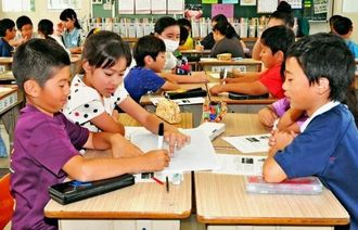 NIE出前講座で、新聞の見出しを考える子どもたち=13日、琉球大学教育学部付属小学校