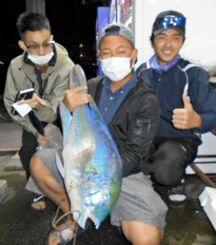 三重城海岸で75センチ、6.87キロのマクブを釣った豊見永理喜さん(中央)=2日