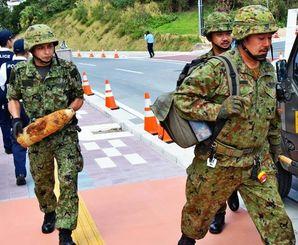 不発弾を手に持ち、回収する自衛隊員ら=4日午後1時8分ごろ、豊見城市・沖縄空手会館前
