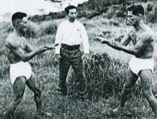 上地完英氏(中央)の下で空手の鍛錬を重ねた友寄隆宏氏(左)=1950年ごろ、宜野湾市野嵩(提供)