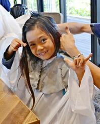 生まれて初めて髪を切り、寄付する予定の小川ジェイちゃん=11月26日、西原町東崎・モアナ バイ ヘッドライト東崎店