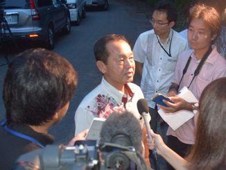 流弾事件の一報を聞き現場付近を訪ね、報道陣の取材に答える渡具知武豊名護市長=21日午後7時35分、名護市数久田