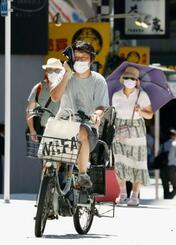 厳しい暑さの中、マスク姿で通行する人たち=11日午前、東京・銀座