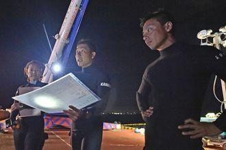 ジャイアントマンタの搬送前に手順を確認する(右から)松本瑠偉さん、金谷悠作さん=15日午後9時前、本部町の通称エキスポ港(金城健太撮影)