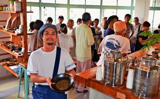 自家焙煎したほうじ茶を手に日本茶の魅力を語る「Roasted Green Tea Apartment EIBUN」の中村栄文代表=那覇市松尾