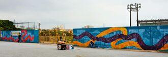 ゲート通りやスケートボードの軌道を描いた壁画の制作作業=6月20日、沖縄市コザ運動公園