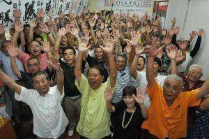 初当選が確実になり支持者と万歳で喜ぶ上原昭氏さん(中央)=5日午後11時26分、糸満市西崎町の選挙事務所
