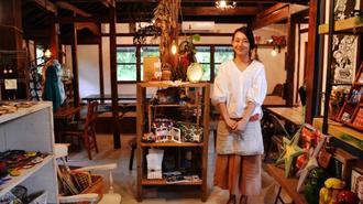 カフェスペースを背に、こだわりの雑貨に囲まれるオーナーの山本真穂さん=名護市運天原
