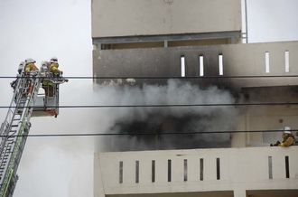 消火活動に当たる消防士ら=15日、那覇市前島