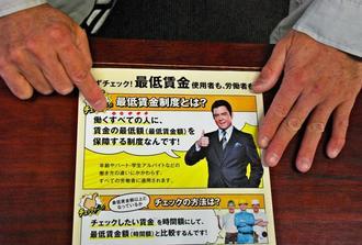 最低賃金の確認を呼び掛けるチラシを手にする山田正彦さん。「『働くすべての人』にぼくらは入っていないのか」