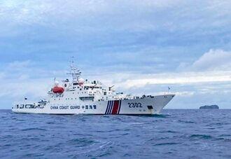領海内で操業する漁師の漁船に、400メートル近くまで接近する中国公船を、漁師が撮影した。奥は尖閣諸島の大正島=8月下旬、尖閣衝突周辺海域