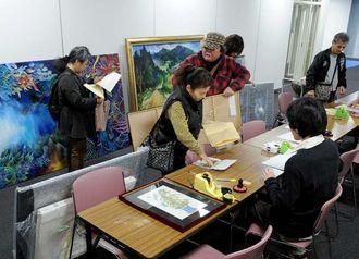 受け付け開始と同時に、作品を搬入する応募者=22日午前、那覇市久茂地・タイムスビル