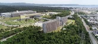 名護市辺野古にある国立沖縄工業高等専門学校。手前の建物が学生寮、左奥が校舎。右奥は米軍キャンプ・シュワブの施設=8日(小型無人機で撮影)