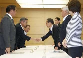 普天間飛行場負担軽減推進会議で、握手する沖縄県の翁長雄志知事(左手前から2人目)と菅官房長官(右手前から3人目)=21日午前、首相官邸