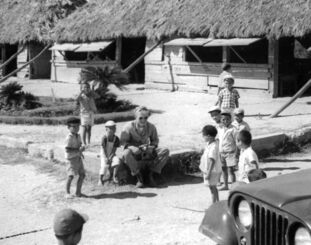 かやぶきの校舎の前で米軍人と話す児童