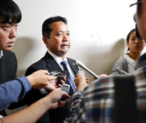県教委の定例会後、記者団の質問に答える平敷昭人県教育長(中央)=日午後、県庁
