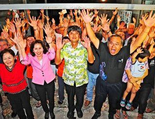 支持者とともにバンザイで当選を喜ぶ東恩納琢磨さん(中央)=7日午後11時55分、名護市瀬嵩