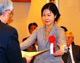 奨励賞の賞状を受け取る新垣綾子記者=9日、東京・内幸町の日本プレスセンタービル
