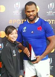 フランス代表のアリベレティ・ラカ選手(右)にトロフィーを手渡した伊礼門千珠さん=10月6日、熊本県民総合運動公園陸上競技場(提供)