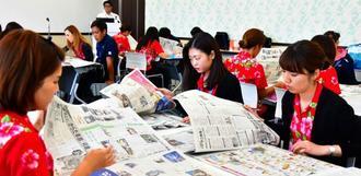 真剣な表情で新聞を読む受講者ら=29日、豊見城市・沖縄ツーリスト豊崎ビル