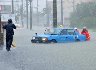 冠水した道路で立ち往生したタクシーを移動させる消防隊員ら=5日午後1時50分ごろ、石垣市真栄里(画像の一部を加工しています)