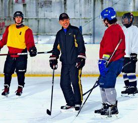 厳しい練習の合間に選手と笑顔で会話する三沢悟監督(中央)