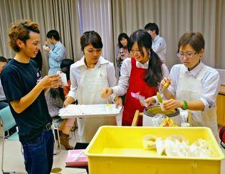 給食グループは発表後、開発したニンジンの揚げパンとポタージュを参加者に提供した=読谷村役場