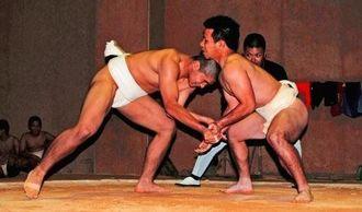 生徒の指名制による教諭との個人対決で、白熱した勝負を見せた島袋亮吉君(左)と石新一早教諭=伊江中学校相撲場
