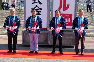 テープカットで沖縄の産業まつりの開幕を祝う実行委の古波津昇会長(左から2人目)と玉城デニー知事ら(同3人目)ら=25日、奥武山公園