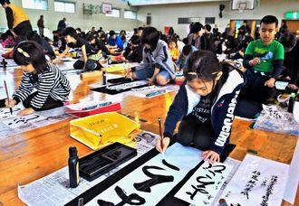 新春かきぞめ大会で「よろこび」の文字などを書き写す子どもたち=糸満市・光洋小学校体育館