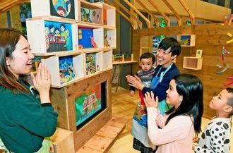 「箱のえほん」に興味津々の子どもたち=9日午後、那覇市久茂地・タイムスビル1階エントランスホール