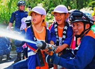 消防士との放水体験に歓声を上げる園児たち=9日、うるま市・具志川ドーム