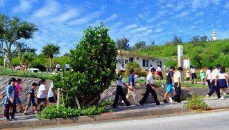 地震・津波の避難訓練で、歩いて高台に移動する北大東小中学校の児童・生徒と幼稚園児ら=11月5日、北大東村中野(同校提供)