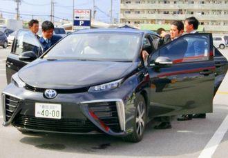 行政や企業関係者が、水素を使った次世代燃料自動車「MIRAI」に試乗し、性能を体感した=北谷町、トヨタグループ北谷ランド