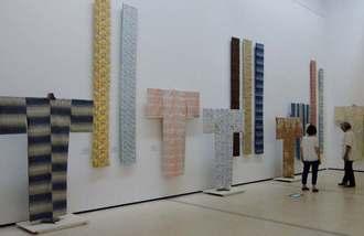 陶芸や染色、織物などの工芸品の設置作業が進められ、最終確認をするスタッフ=12日、那覇市・県立博物館・美術館