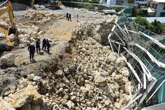 積み石が崩落し、土木作業員の男性が死亡した事故現場を調べる捜査員ら=16日午前10時55分ごろ、北中城村安谷屋