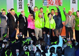総決起大会で必勝を誓いガンバロー三唱で気勢を上げる末松文信氏(中央)と支持者=9日午後8時21分、名護市民会館