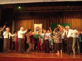屋宜宣太郎さん(中央)の叙勲受章を祝って、カチャーシーを踊る県人会関係者ら=在亜沖縄県人連合会館