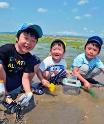 潮干狩りを楽しむ大下美和(よしかず)さん(左)と弟たち=7日午後、うるま市・海中道路近くの海岸(崎浜秀也撮影)