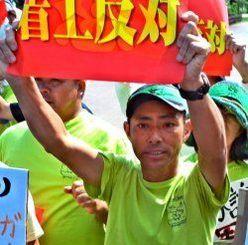 与那国沿岸監視隊の起工式で「着工反対」のビラを掲げて抗議する稲川宏二さん=2014年4月19日、与那国町