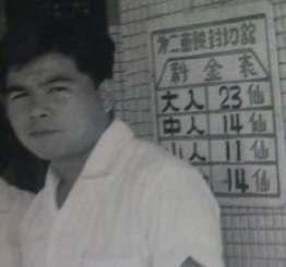 旧名護町内の映画館で働いていた頃の比嘉さん。後ろには料金表もみえる=1960年ごろ