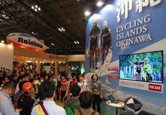 風光明美なコースや冬でもサイクリングを楽しめる沖縄の魅力について聞き入る来場者ら=千葉県・幕張メッセ
