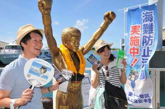 ライフジャケットを着用した具志堅用高さんの銅像と記念撮影する観光客=石垣市・石垣港離島ターミナル