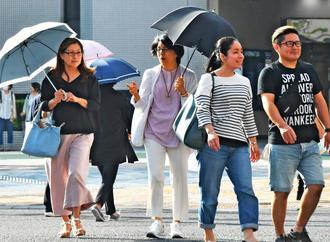 暑さを避け、日傘を差して歩く姿が目立った交差点=6日午後3時20分ごろ、那覇市久茂地(田嶋正雄撮影)