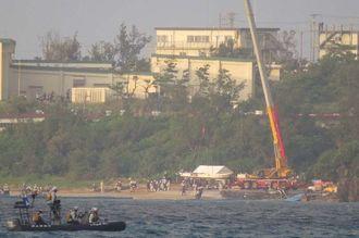 ブイ設置に向け、作業船を海上に下ろす大型クレーン=14日午前6時31分、名護市辺野古