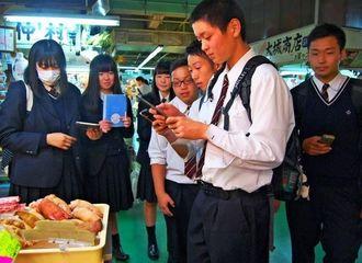 写真を撮り、アプリに取り込みながら街の移り変わりを学ぶ静岡県立裾野高校の生徒たち=27日、那覇市・第一牧志公設市場