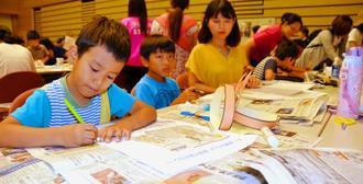 切り取った新聞記事について感想を書く子どもたち=北谷町・ちゃたんニライセンター