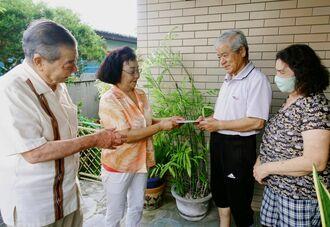 民生委員の活動を知らせる(左から)比嘉朝文さん、新崎悦子さん=3日、那覇市首里崎山町