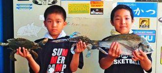 泡瀬漁港で40.9センチ、1.24キロのチヌを釣った赤道小学校6年の大久保一騎(右)くんと島袋玲和くん=2日