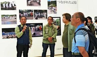 報道カメラマン写真展で作品の解説をする大城弘明さん(左)と山城博明さん(同2人目)=28日午前、県立博物館・美術館